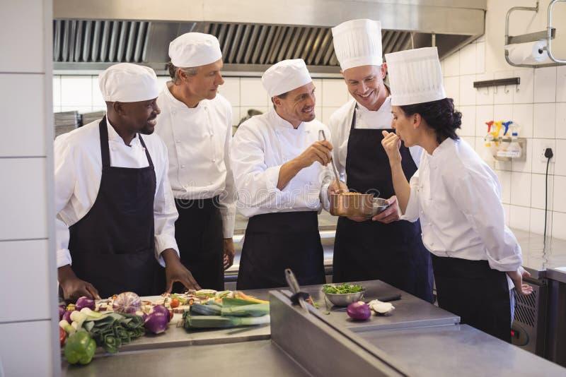 厨师品尝食物队在商业厨房里 免版税库存照片