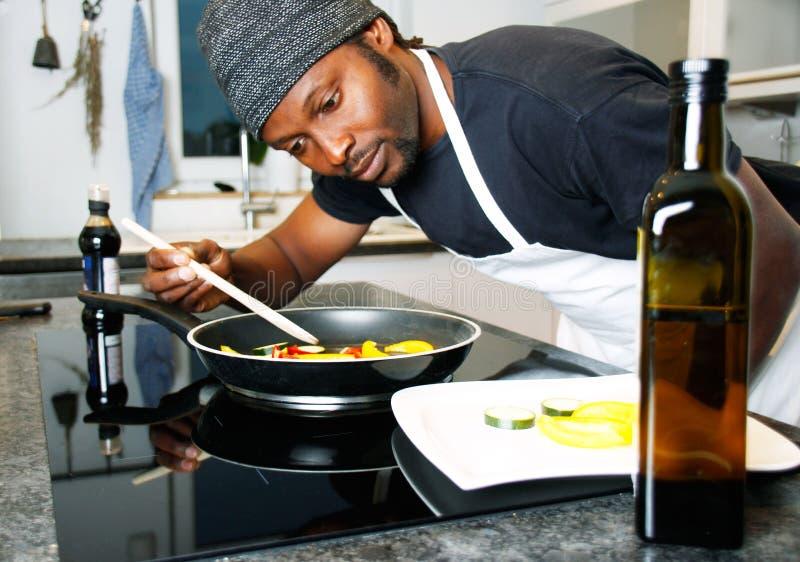 厨师在准备一顿特别膳食的餐馆厨房里 库存照片