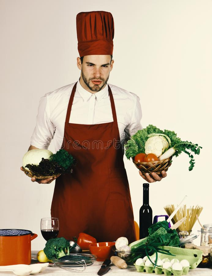 厨师在厨房里工作在与菜和工具的桌附近 制服的人拿着成份 食物配制概念 库存照片