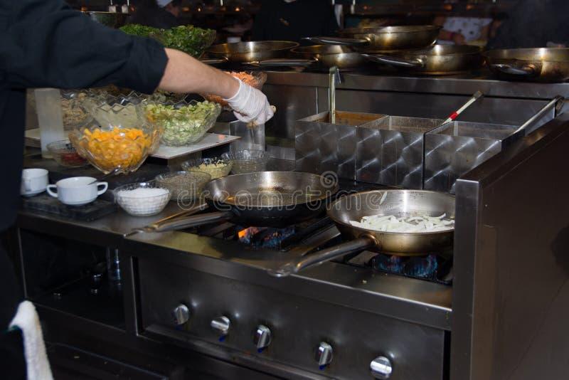 厨师在火炉的餐馆厨房里与平底锅,做在食物的flambe 低ligth选择聚焦 免版税库存照片