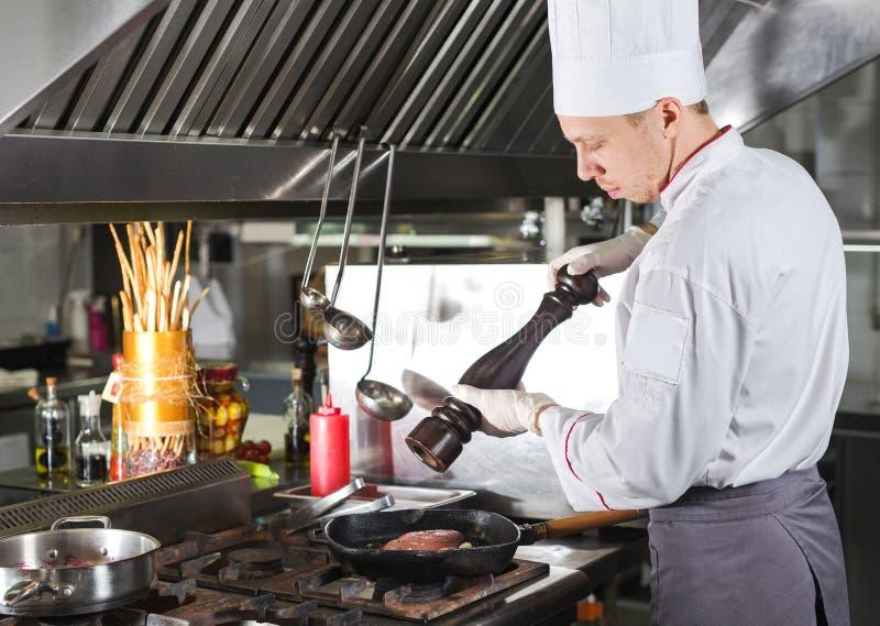厨师在火炉的餐馆厨房里与平底锅,烹调 免版税库存照片