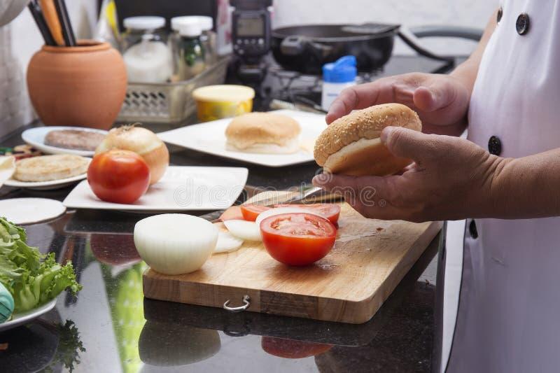 厨师在烹调汉堡包前的准备的汉堡 免版税库存照片