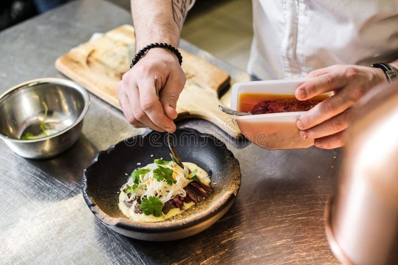 俄罗斯,圣彼德堡,03 17 2019厨师在餐馆厨房里准备牛排里脊肉 免版税库存图片