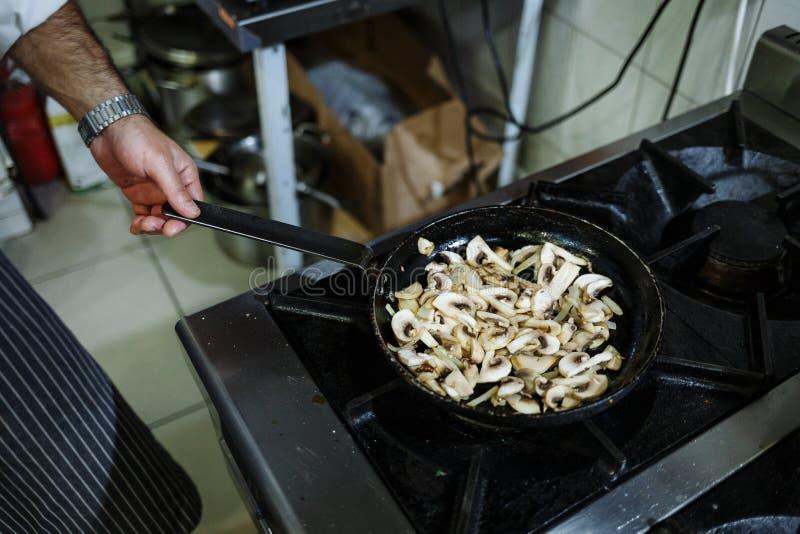 厨师在餐馆厨房里油煎在一个平底锅的蘑菇在煤气炉 免版税图库摄影