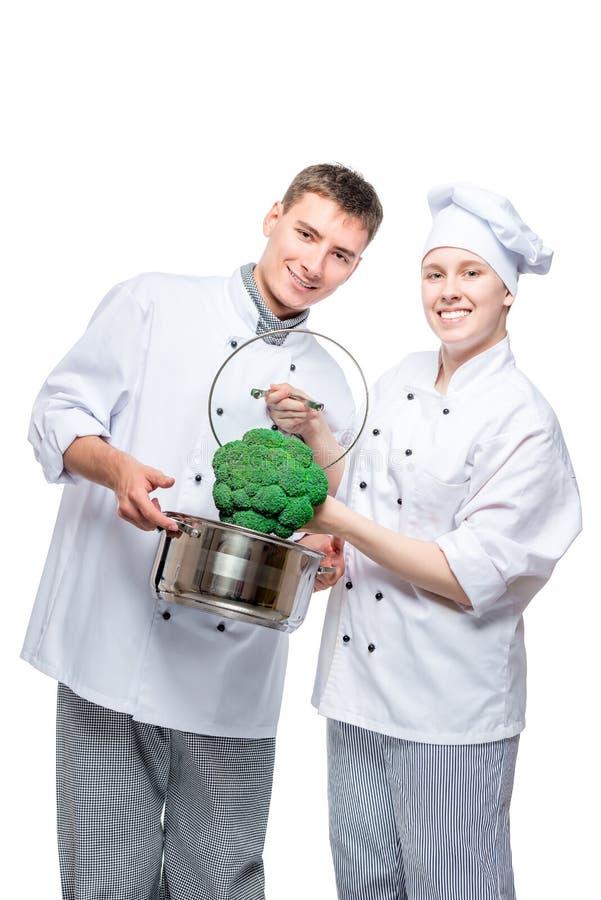 厨师垂直的画象有平底锅和硬花甘蓝的在白色 免版税库存照片