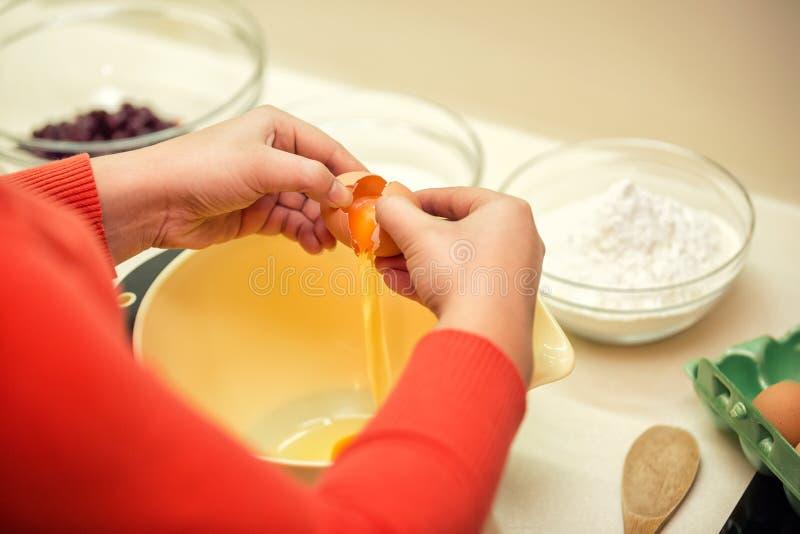 厨师增加蛋糕的蛋混合物 免版税库存图片