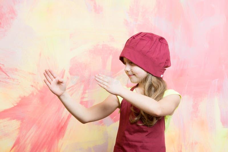 厨师帽子的与空手道手势的女孩和围裙 免版税库存照片