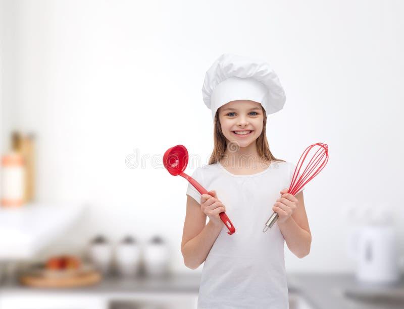 厨师帽子的微笑的女孩有杓子的和扫 免版税库存照片