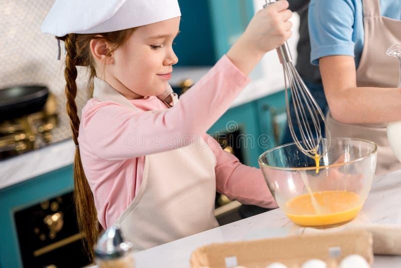 厨师帽子的搅拌鸡蛋的孩子和围裙 库存图片