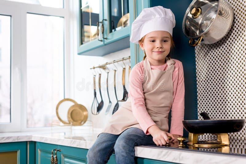 厨师帽子的逗人喜爱的微笑的看煎锅的孩子和围裙 库存图片
