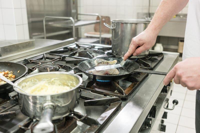 厨师或厨师在油煎在平底锅的餐馆鲤鱼鱼在火炉 图库摄影