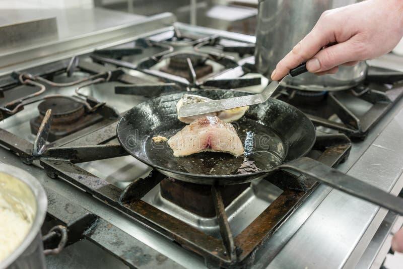 厨师或厨师在油煎在平底锅的餐馆鲤鱼鱼在火炉 免版税库存图片