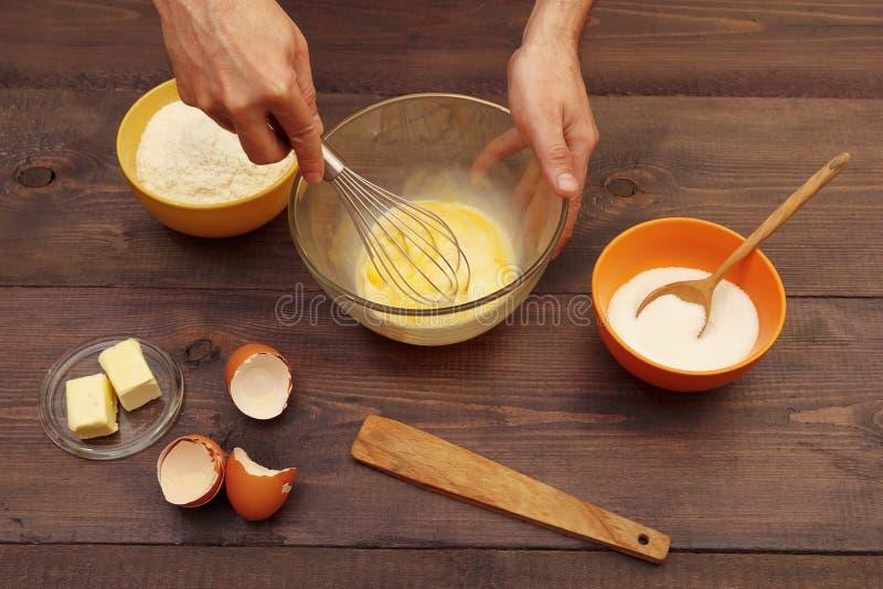 厨师手揉与飞奔的面团在木桌上的碗 免版税库存图片