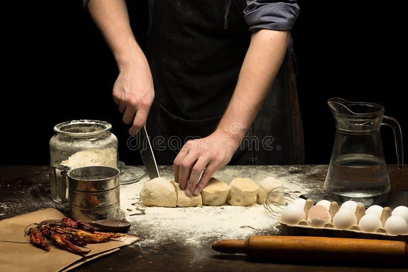 厨师手由刀子切了薄饼的面团 免版税库存照片
