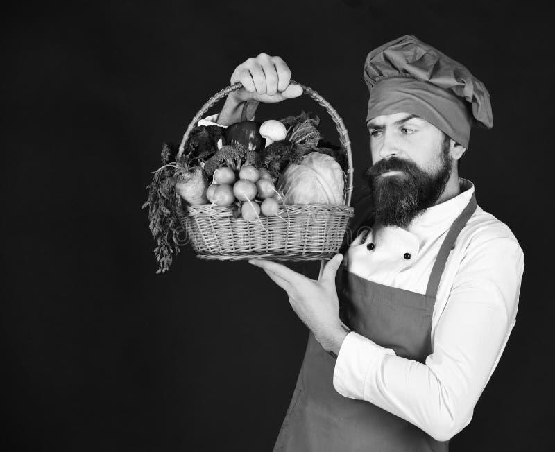 厨师拿着圆白菜、萝卜和莴苣 有胡子的人拿着在黑背景的素食者 免版税图库摄影