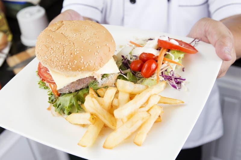 厨师提出了汉堡包板材  库存照片