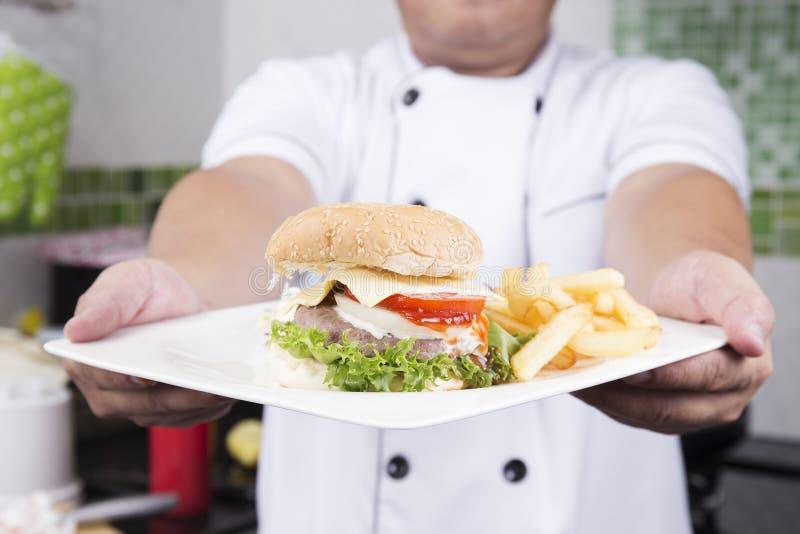 厨师提出了汉堡包板材  图库摄影