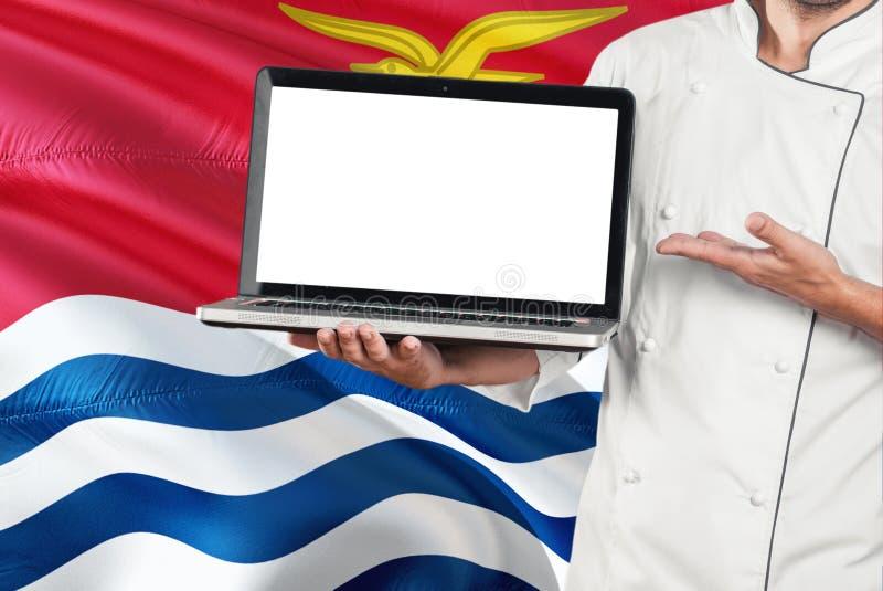 厨师有黑屏的藏品膝上型计算机在基里巴斯旗子背景 烹调佩带的制服和指向膝上型计算机拷贝空间的 免版税库存照片