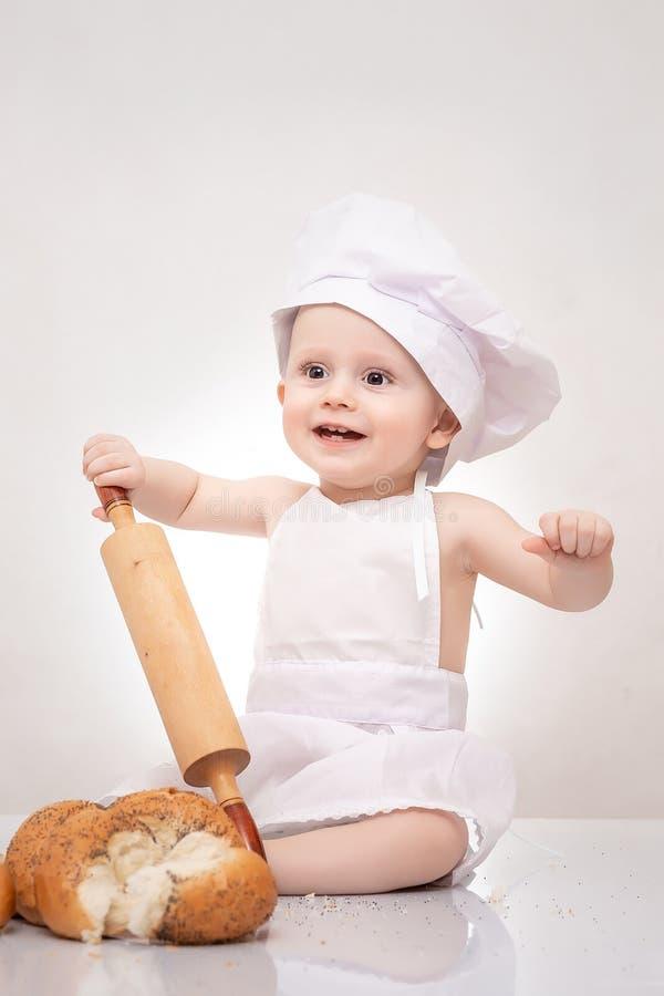 厨师服装和厨师帽子的滑稽的厨师婴孩有面团坐用面包的滚针的 免版税图库摄影