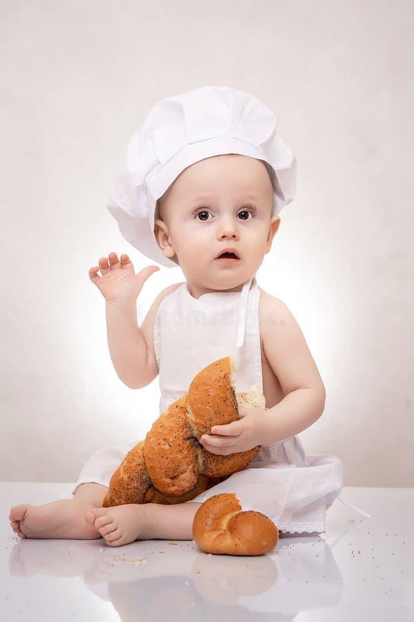 厨师服装的小男孩用面包 愉快笑 免版税库存图片