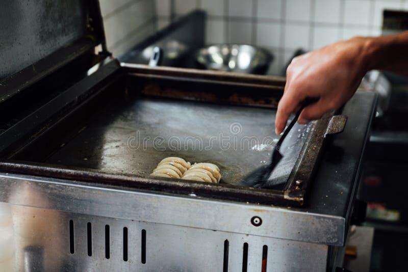 厨师油煎的矢木Gyoza日本Pan-Fried饺子 热,新鲜,水多和鲜美 库存照片