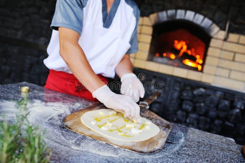 厨师涂黄油和乳酪在薄饼的基地 库存照片