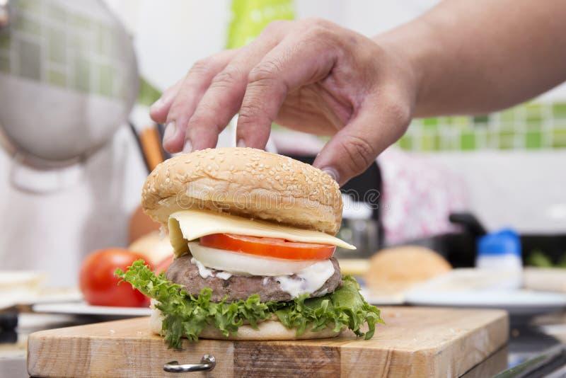 厨师烹调和装饰的汉堡包 免版税库存图片