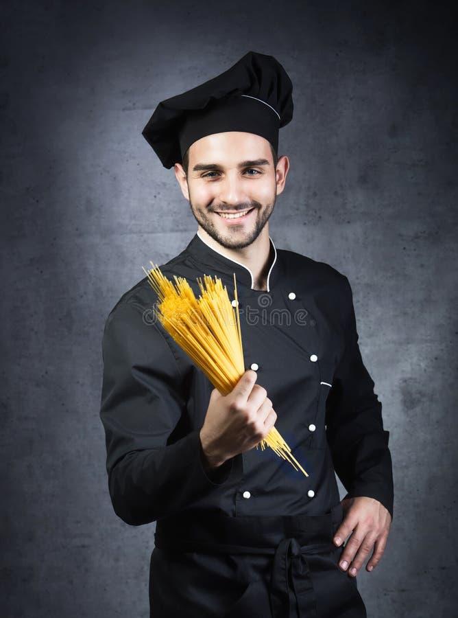 厨师烹饪器材的画象在黑制服的有意粉的 库存图片