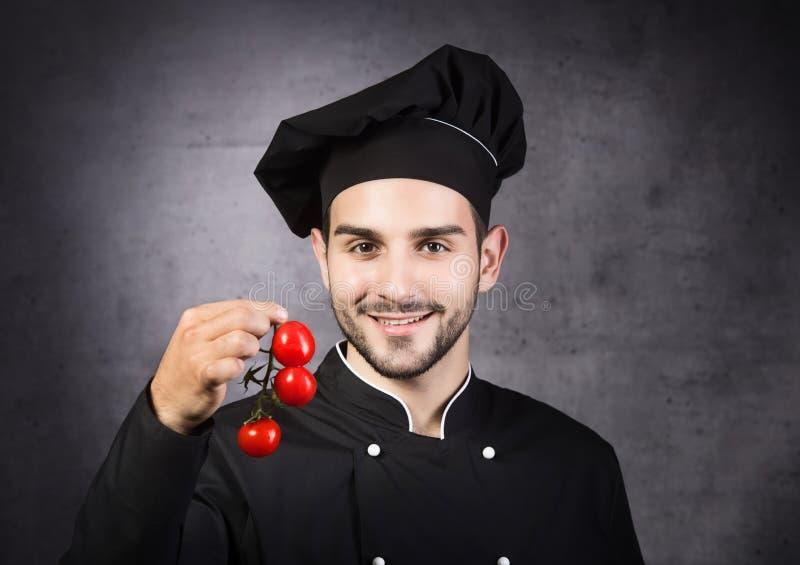 厨师烹饪器材的画象在黑制服的用蕃茄 免版税库存照片