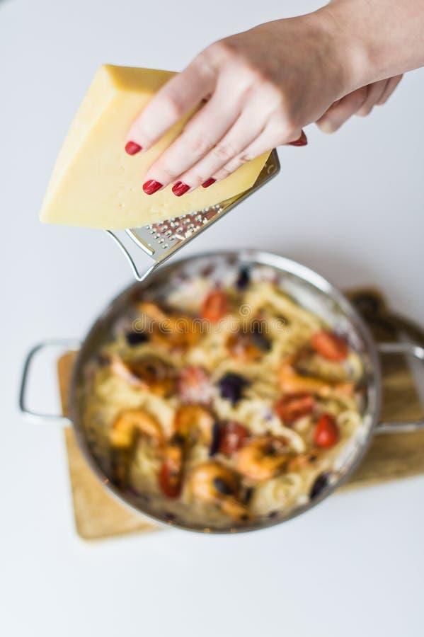 厨师用虾摩擦巴马干酪面团 r 免版税库存照片