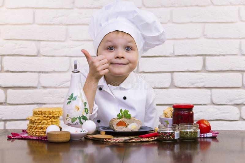 厨师男孩烹调了肉卷用红萝卜和鸡蛋 免版税库存图片