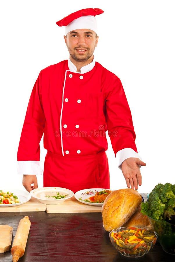 厨师男性显示的食物在厨房里 库存照片
