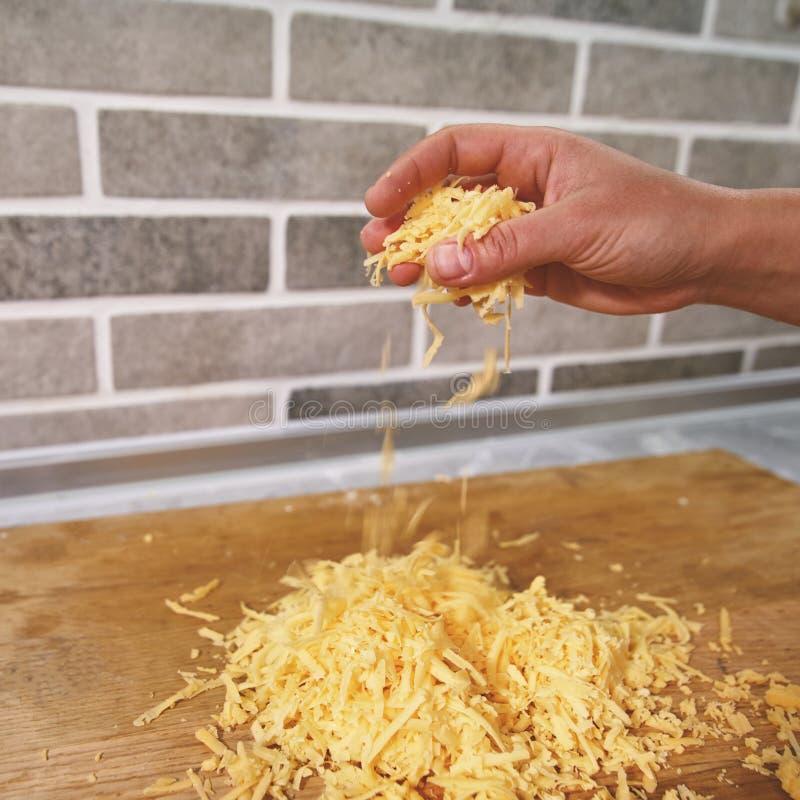 厨师的手倾倒在一个木板之上的被击碎的乳酪 库存图片