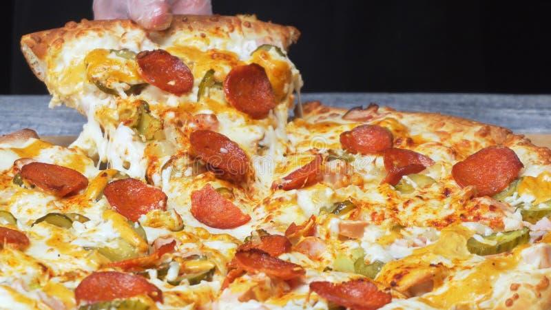 厨师的手特写镜头在采取可口新鲜的那不勒斯的比萨的片断与熟的干香肠圈子的硅树脂手套的  库存图片
