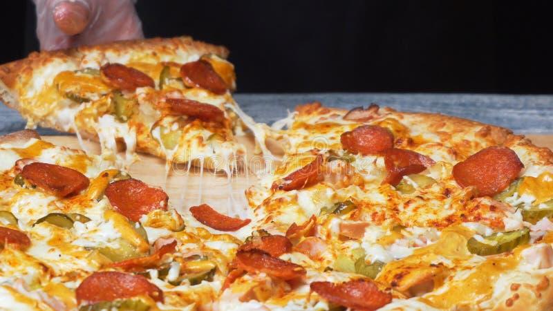 厨师的手特写镜头在采取可口新鲜的那不勒斯的比萨的片断与熟的干香肠圈子的硅树脂手套的  图库摄影