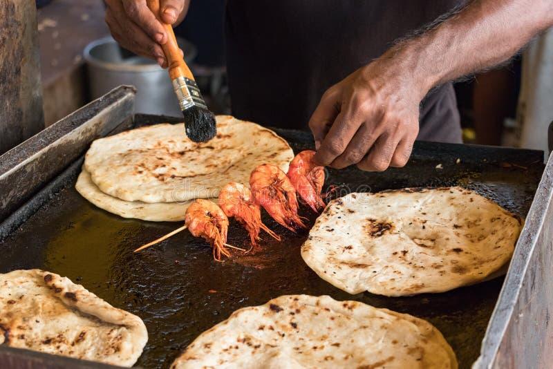 厨师的男性手,烹调大虾用波尔布特roti平的面包tn加勒食物街市在科伦坡,斯里兰卡面对st博士 库存照片