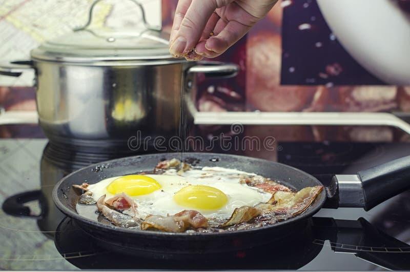 厨师盐溶在煎锅的荷包蛋,烹调烟肉,并且在煎锅的荷包蛋,烹调在厨房里,投入 库存照片