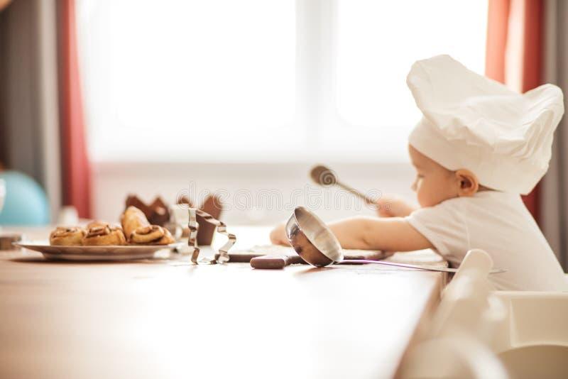 厨师盖帽的可爱的矮小的小孩男孩,使用与松饼罐子在桌上 免版税库存图片