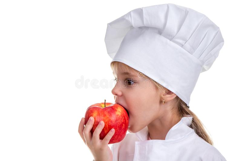 厨师盖帽的女孩咬住红色苹果的 健康食物和健康生活方式的概念 外形图象 库存照片