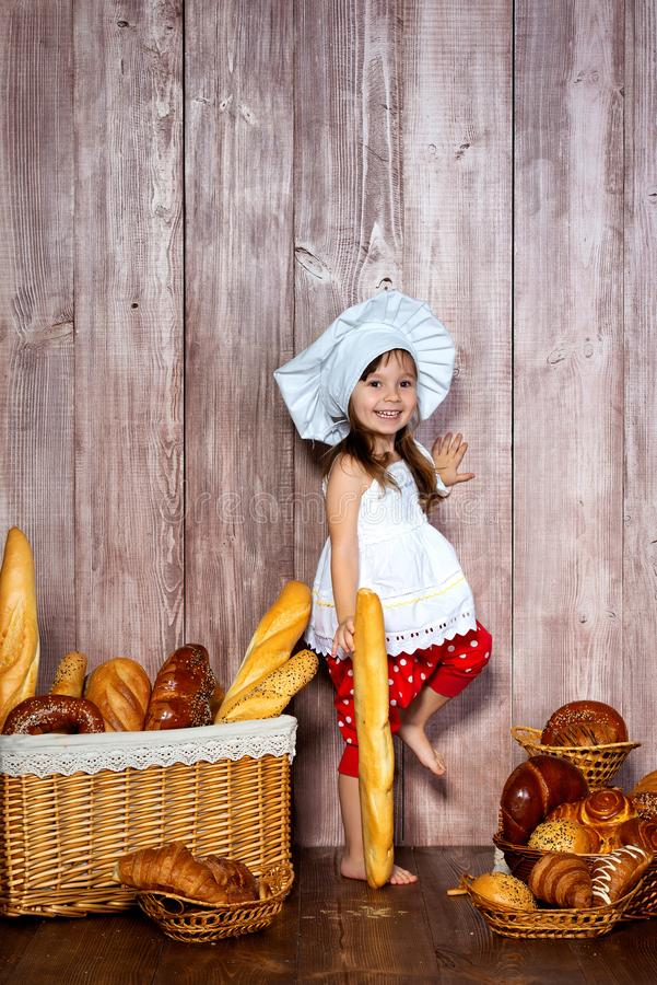 厨师盖帽的逗人喜爱的矮小的微笑的女孩在与小圆面包和面包店产品的一个柳条筐附近站立 免版税库存图片