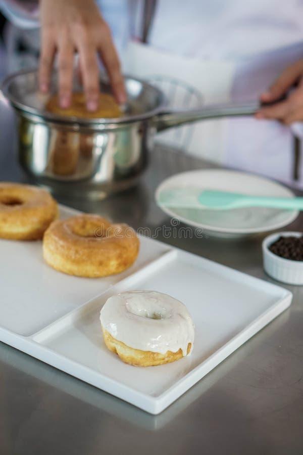 厨师给上釉的油炸圈饼 免版税库存图片
