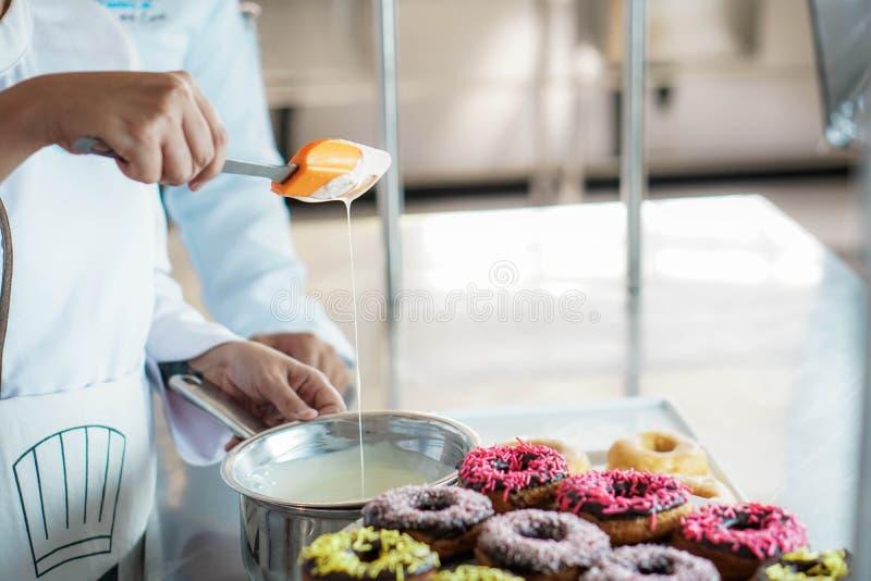 厨师给上釉的油炸圈饼 库存照片