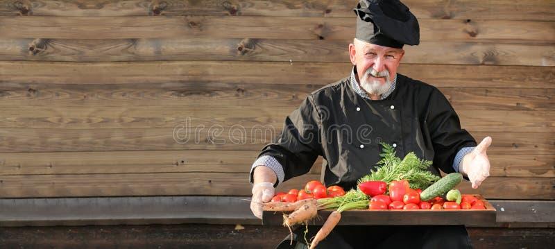 厨师老在有菜的制服 免版税库存图片