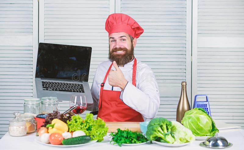 主厨笔记本电脑阅读烹饪食谱 烹饪学校 戴帽子的嬉皮士学习如何在线烹饪 烹饪 库存图片