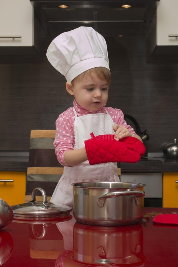 厨师衣服的逗人喜爱的矮小的婴孩和一副红色手套在厨房里烹调 免版税库存图片