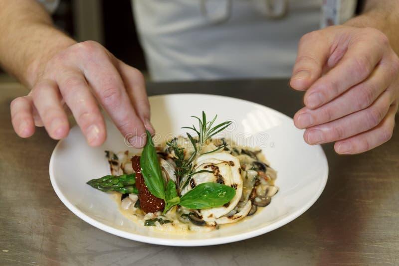 厨师装饰意大利煨饭 免版税图库摄影