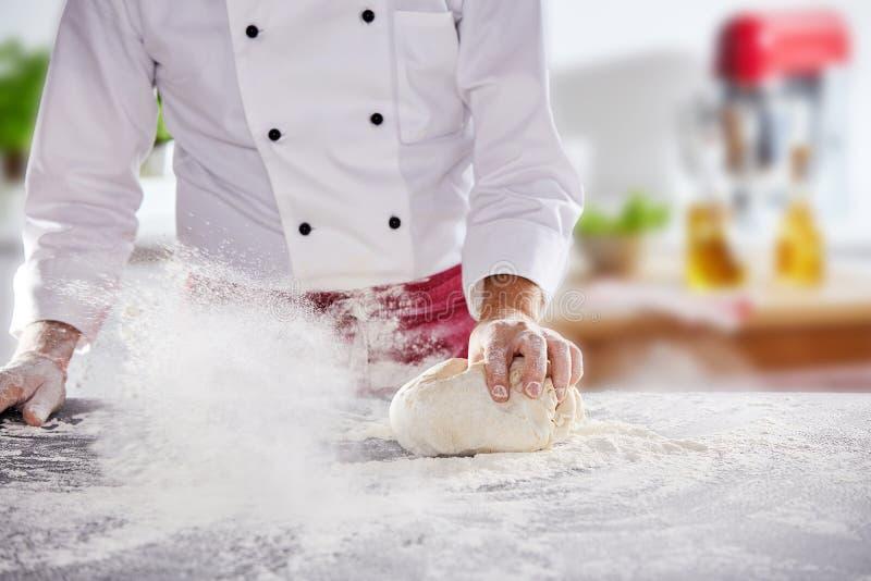 厨师辗压面团在白面 库存图片
