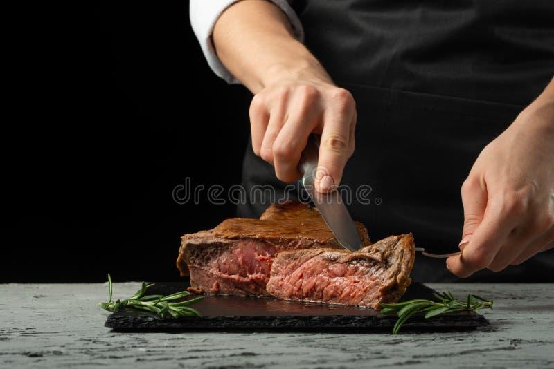 厨师,切用在黑背景的肉牛排,自创食物的食谱概念 一个更大的计划 免版税库存照片