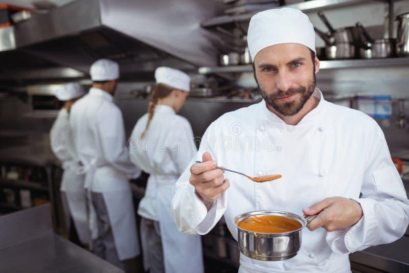 厨师从匙子的品尝食物在餐馆的厨房里 图库摄影