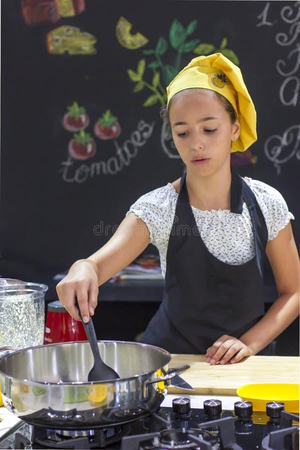 厨师` s帽子的女孩在黑色的大平底深锅烹调 库存照片
